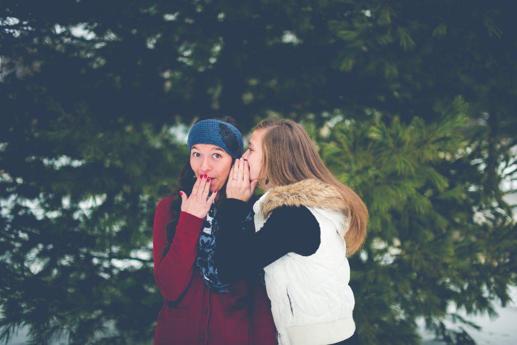 Women telling a secret.